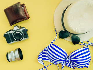 flat lay group for summer cloth and accessories (blue bikini girl , camera , wallet) with yellow background