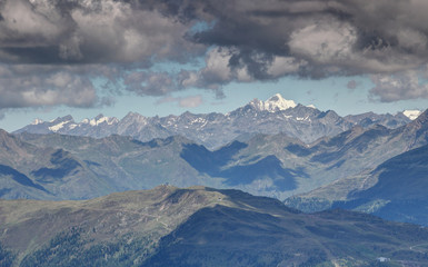 Gray clouds over snowcapped Rotspitze Pizzo Rosso peak and sunlit gray rocky ridges of Venediger Group and Villgraten Mountains Defereggen Alps Hohe Tauern East Tyrol Austria Europe
