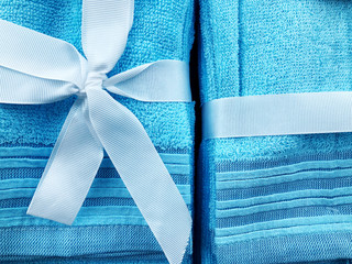 A blue towel bound by a blue bow kaak background for anything. Present for women.