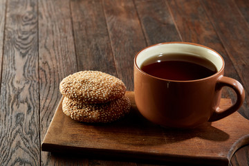 Cup of tea with cookies on a wooden cutting board on vintage background, top view