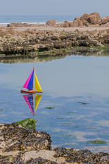 The colorful children's ship on small water at low tide in the bay of Somme, France