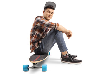 Teenage skater boy sitting on a longboard