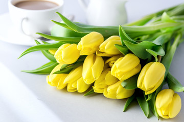 Beautiful Yellow Tulips on Blue Background Cup of Coffee Breakfast Morning Holiday Birthday Composition