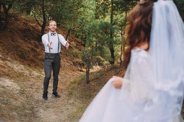Groom hugging his laughing bride in green park