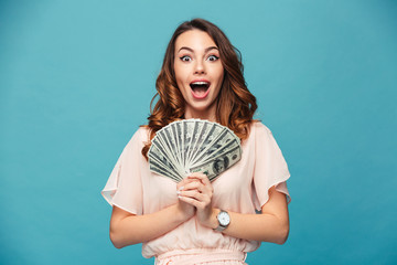 Excited young lady showing money.