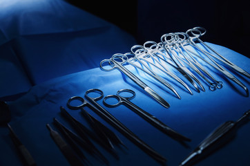 selective focus surgical instrument lying on table while group of surgeon work in operation room at hospital, emergency case, surgery, medical technology, health care cancer, disease treatment concept