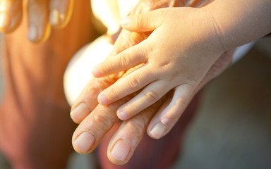 hand of little girl holding hands of old woman.