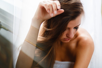 The girl with long hair sitting and crying, smearing mascara and tears on her face. A weeping woman holds her head with her hand in frustration from losing or parting or breaking up a relationship.