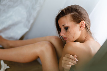 Sad woman hug her knee and cry,sadness tone picture. A weeping woman holds her head with her hand in disappointment from losing or parting or breaking up a relationship.