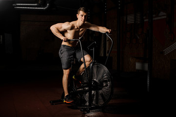 Young and handsome man practicing crossfit using an exercise equipment in a gym