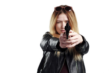 A girl in a leather jacket holds a revolver in her hands, danger, self-defense. The image of a confident and strong woman