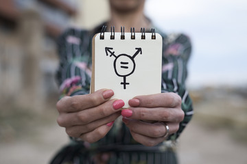 woman shows notepad with a transgender symbol