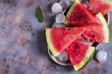 slices of watermelon on a iron plate with ice
