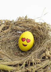 Two Easter eggs painted with emojis, one in love and other kissing, placed into a nest in isolated white background