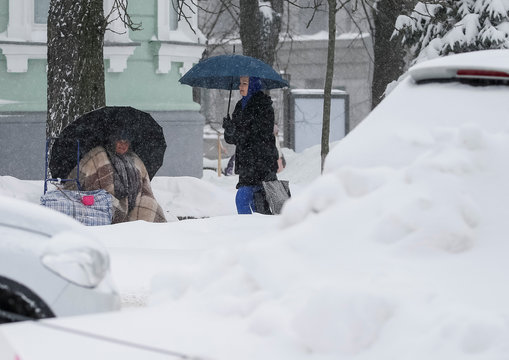 A woman begs for money ehile another woman walks past cars parked along a snow-covered street as snow falls in central Kiev