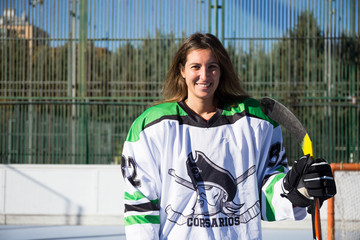 Cheerful sportswoman standing with hockey stick and looking at camera.