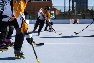 Unrecognizable players having competition while playing in-line hockey on rollers in sunny day.