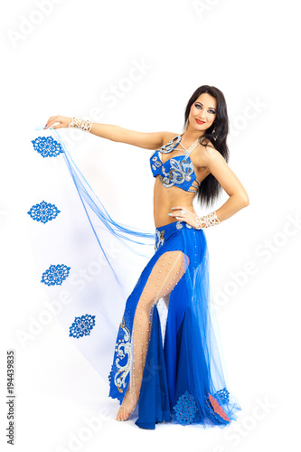 4e19c7404 A young dancer in blue clothes performs an oriental belly dance. Isolate.  Beautiful girl in bright national clothes dancing on white background.