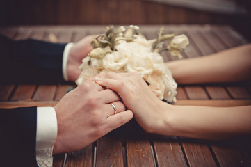 Bridal bouquet of roses and newly-married couple hands on a wooden background