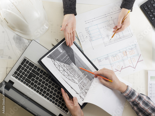 Architects working on blueprint real estate project architect architects working on blueprint real estate project architect workplace architectural project blueprints malvernweather Choice Image