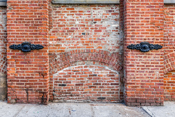 Brick wall in Brooklyn, NYC, New York City front view exterior, grunge old architecture dirty by sidewalk