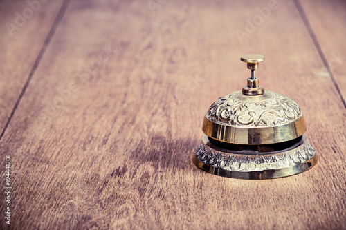 Vintage Bronze Hotel Reception Service Desk Bell On Wooden Table Background Old Retro Style Filtered