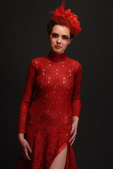 brunette in red lace dress on a dark background