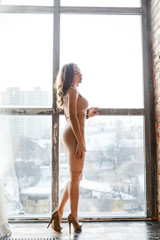 fashion indoor portrait of elegant sexy woman in luxurious sequins dress near the window