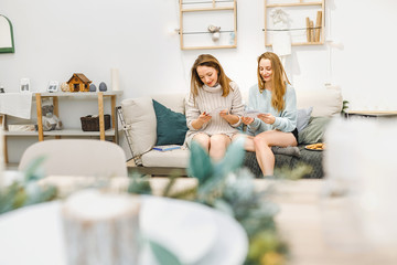 girls friends relaxing and looking at the photo album in their apartment