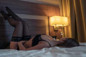 A girl with a beautiful figure in sexy lingerie lies on a bed