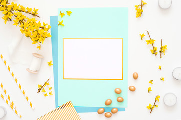 Easter spring composition with card, flowers and chocolate eggs on white background, space for text