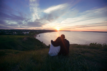 Couple in love on the hill looking at the sunset at Kama Mouth in Tatarstan