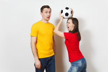 Fun crazy cheerful European young couple, woman, man, football fans in yellow red uniform hold play soccer ball isolated on white background. Sport, game football, family leisure, lifestyle concept.