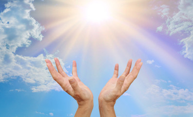 The Awesome Sun and its Natural Healing Source of Energy - healer's hands outstretched reaching up towards a bright sunburst beaming down with blue sky and fluffy clouds