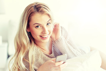 happy young woman with smartphone in bed at home