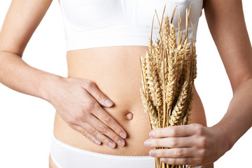 Photo sur cadre textile Graine, aromate Close Up Of Woman Wearing Underwear Holding Bundle Of Wheat And Touching Stomach