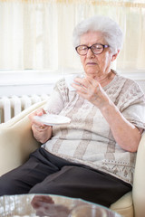 Portrait of senior woman sitting on armchair and drinking coffee at home.