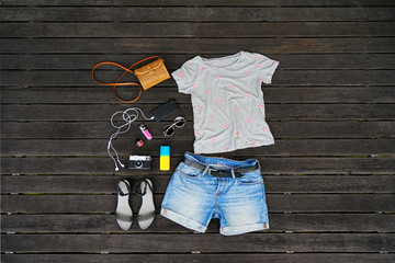 Woman summer clothes collage flat lay isolated on dark wood background. Feminine desk top view fashion accessories: t-shirt, shorts, sandals, sunglasses, vintage photo camera, headphones. Holiday