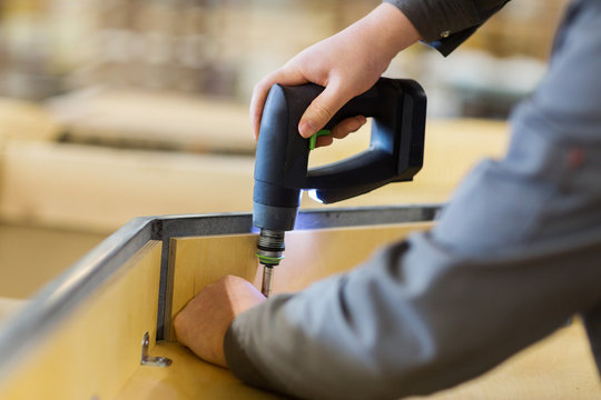 assembler with screwdriver making furniture
