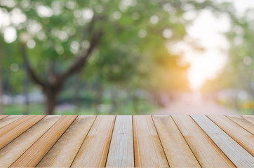 wood board or wood table with green blur bokeh background in nature park with copy space for product adverticing text.
