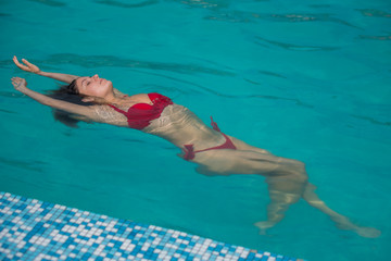 young attractive woman in red swimwear in pool with head thrown back side view. Young sexy woman with pretty face and wet hair swimming in pool with blue water sunny summer day outdoor