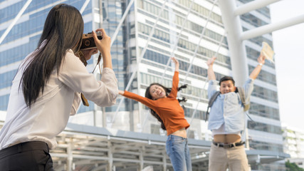 business woman hold camera to shoot the traveler couple people at urban city and modern building. Honeymoon trip, holiday vacation travel concept.
