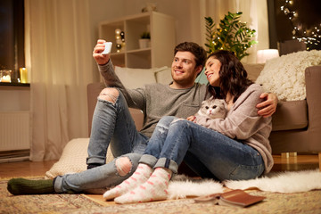 happy couple taking selfie by smartphone at home