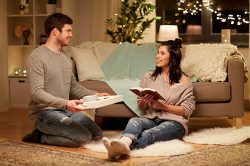 happy couple with book and food at home