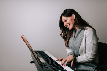 Smiling woman pianist playing synthesizer from sheet music.