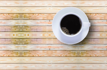 top view of black coffee in white cup on wooden board.