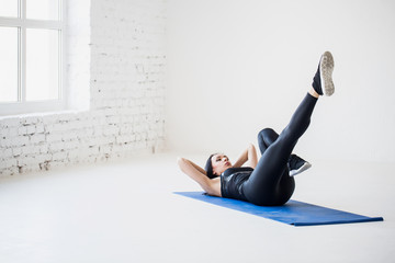 Back view of the sports lade warming up by lying on the exercise mat and doing bicycle crunches in the isolated white studio.
