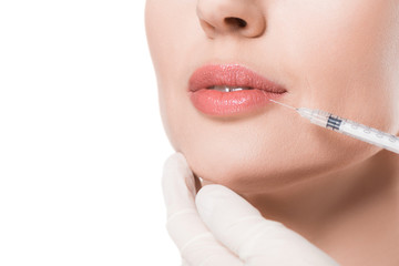 Closeup view of beautician hands doing injection in woman lips isolated on white
