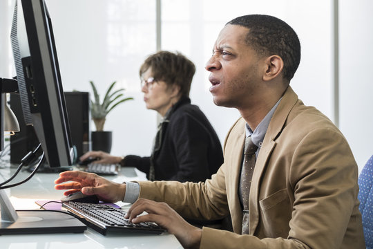 Business man working on computer looking frustrated, upset