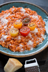 Tomato risotto topped with fresh sliced mini tomatoes and grated parmesan, selective focus, close-up